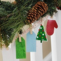 Christmas-shaped cardstock items pinned to a ribbon with clothespins