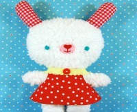 a white stuffed bunny wearing a red polka-dot dress