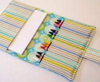 a wallet made of striped material to hold paper and crayons