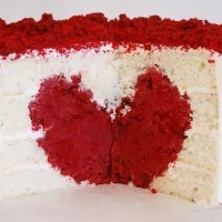 A white cake with a red heart inside