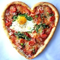 A heart-shaped pizza with an egg on top