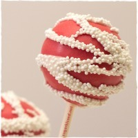 A red cake pop with strings of white sprinkles on it