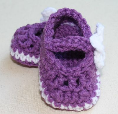 Purple Mary Jane booties with a white decorative flower on one side