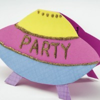 A party invitation shaped like a spaceship