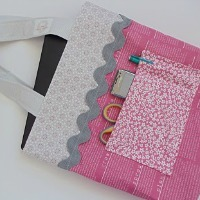 A tote bag made from pink, gray, and flowery fabric