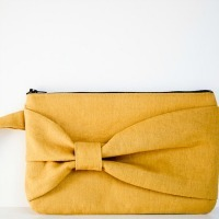 A yellow clutch bag with a bow on the front