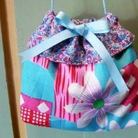 A purse made from flowery fabric with a ribbon on top and a drawstring