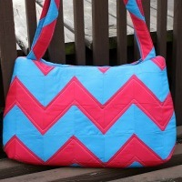 A large purse made from pink and blue stripes of fabric