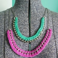 Two crocheted necklaces, one green and one purple, each with a chain intertwined with thread