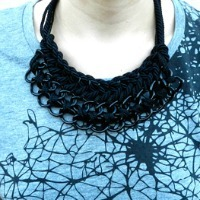 A black necklace made of threaded, braided yarn