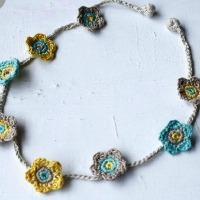 A necklace made of several crochet flowers on a string