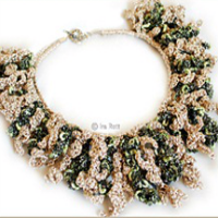 A necklace made of green and cream thread, crocheted to look like coral reef