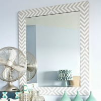 A mirror with a striped herringbone border