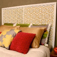 A bed with a white headboard made up of geometric designs