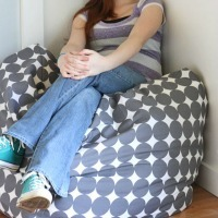 A young girl sitting on a polka dot oversized pouf