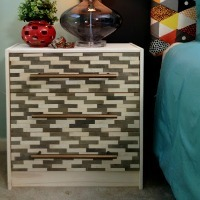 A white nightstand with a wooden mosaic decorating the drawer fronts