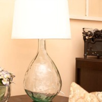A glass lamp with a white lampshade