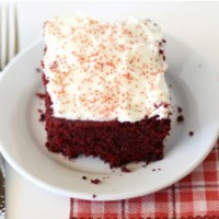 Red velvet cake with white frosting and red sprinkles