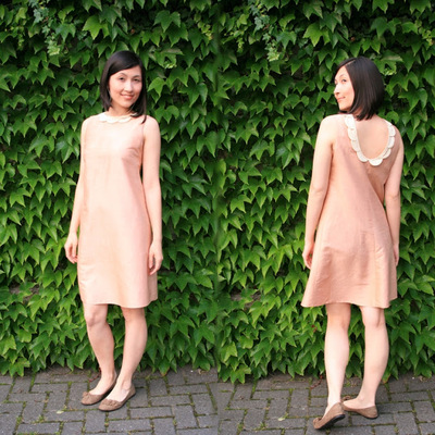 Woman wears shift dress with scalloped collar