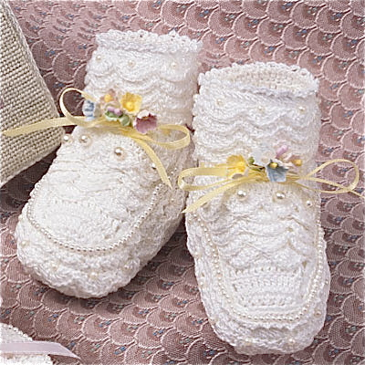 An accessorized baby bootee with beads and ribbon