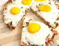 Breakfast pizza with eggs, ham and mozzarella