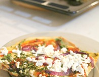Hummus pizza with feta cheese, cumin and arugula