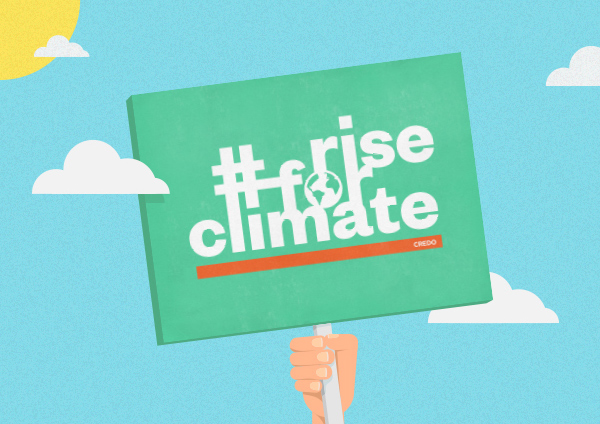 Rise for Climate sign being held against a blue sky