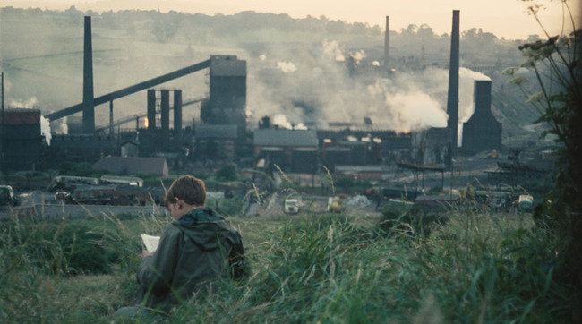 Still image from 1969 film Kes of boy sitting in an industrial landscape in the UK