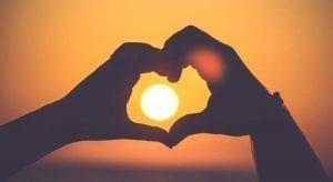 solar power - sun viewed through hands forming a heart