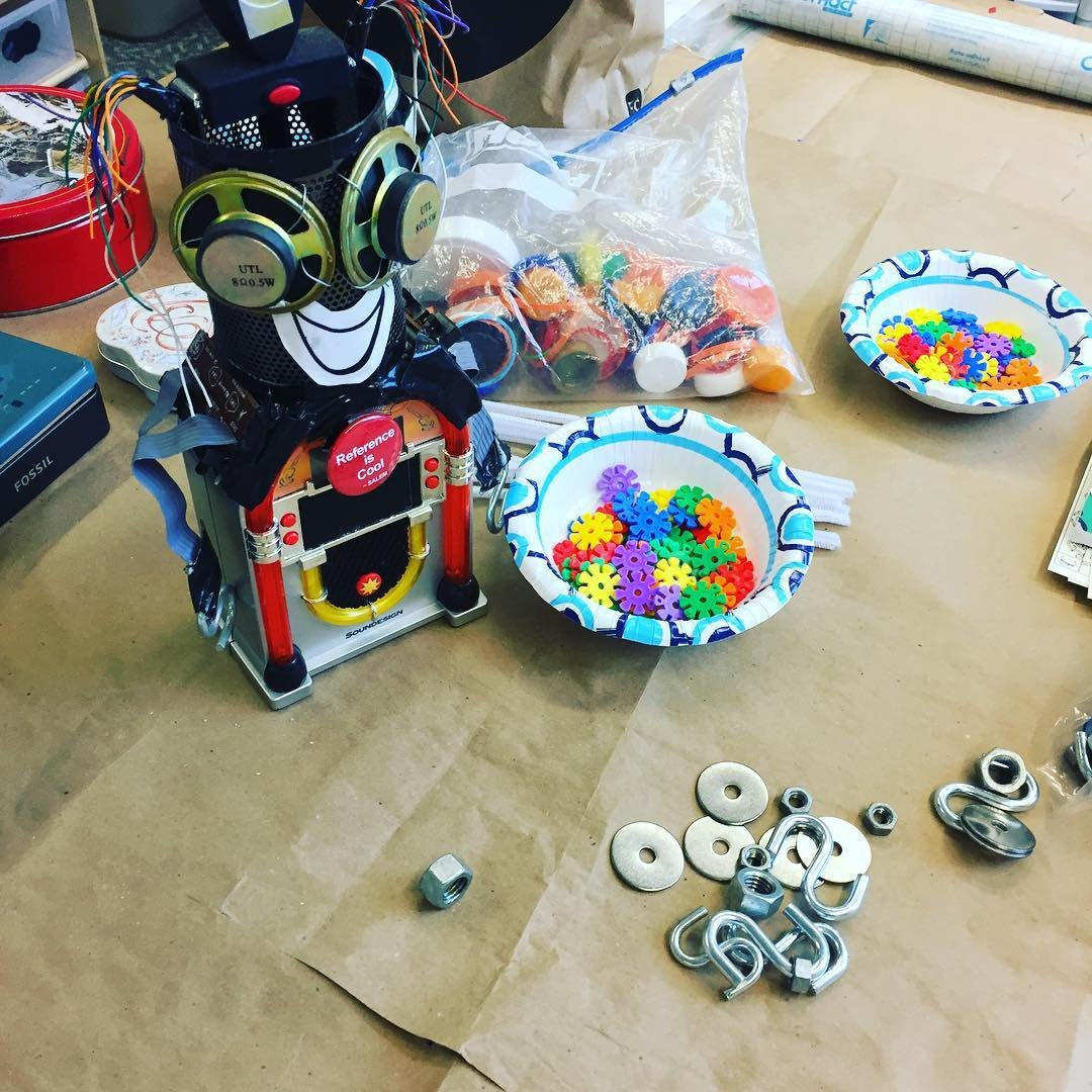 Photo by user monroevillepubliclibrary, caption reads Make and take Tuesday! Drop in the Create Space anytime from 4-6pm to make your own robot!! Some assembly required 😉 #librariesofinstagram #makerspace #robots
