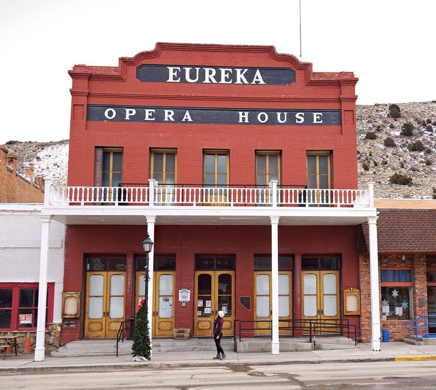 "The Loneliest Road In America Conqueress Challenge: Eureka Opera House (8 of 10) • There's a lot of 1800's history in Nevada with gold mines, ghost towns, local caves, and more. This is an auditorium and convention center in Eureka Nevada. Their first silent film was shown in 1915. I love the sign that they are the friendliness town on The Loneliest Road In America. I wanted to stop by Pony Express Deli for healthy snacks but they were closed on Sundays. • Click link in bio to download your FREE copy of ""The Loneliest Road In America"" Conqueress Challenge map for your next road trip in Nevada! • #travelnevada #DFMI #weirdnevada #eurekaoperahouse #naturalnevada #explorenevada #thesouthwestconqueress #conqueresschallenge #wanderlust #roadtrip #westbysouthwest #YesVacayUSA #nevadamagazine #desertlife #theloneliestroadinamerica"