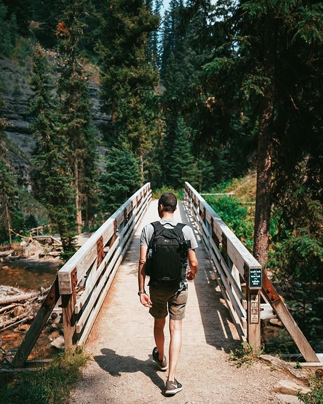 """Photo by user hikeology, caption reads """"it's impossible to walk in the woods and be in a bad mood at the same time"""" - not sure where that saying originated, but i know it's 💯 percent true. this trip was not perfect by any means, from flight delays, to car trouble, to wildfires and thunderstorms 😑 i'll admit, there were moments when we thought this trip was cursed. but when life gives you low visibility and skies raining ash - hike to a waterfall 🤷🏼♀️ amiright? the beautiful hike to ousel falls was a wonderful distraction to all our travel woes and a great reminder to stop worrying and live in the moment ✨ . . if you happen to find yourself in big sky this is a great 1.6 mile hike with a big reward for fairly little effort. if you head out on the trail, pack some snacks (and remember to pack out your trash!) - the trail is very well maintained and sprinkled with picnic tables along the way. . . . #hikeology #amateuradventurer #hike #hiking #hiker #hikelife #hikemontana #hikebigsky #bigsky #bigskyhikes #montanahikes #lonemountain #bigskymeadow #ouselfalls #ouselfallspark #getoutside #exploremontana #roadtrip #travel #waterfallhike #gallatinriver #gallatingateway #sonyalpha #sonya7ii #sonyalpha7ii"""
