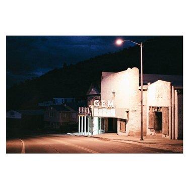 Pioche, Nevada. Gem theater 📷 Leica r5 50 mm Kodak Portra 400 dev et scan @studioargentique . Pioche, la véritable ville de l'Ouest avec sa seule rue, son unique hôtel dont le lobby fait office de bar et bien sûr son Dinner. On retrouve les cowboys au grill du Silver Café avant de finir la soirée le long du saloon avec eux, une Coor's light à la main. Quelle simplicité que Pioche nous faisait vivre en ce dimanche soir de janvier. Une petite ville bâtie autour d'un cimetière où sont enterrés les premiers habitants, tous partis d'une mort violente suite à un duel de trop.  Les coups de revolver doivent encore résonner sur le bout de bois qui a servi comme pierre tombale et que le climat sec a permis de conserver. Ce soir on entend que les boules de billards et les chahuts des habitués. Les machines à sous prennent la poussière au fond de la salle. Les cow boys savent bien que l on ne gagne jamais vraiment. Il faudra penser à les débrancher à un moment donné. Ce soir on avait pris une rousse et une IPA, pas de Coor's light et on passait pour des gens pas vraiment du coin. Des touristes du dimanche en somme. . #leicar #leicar5 #magazine35mm #thedaily35mm #ihsp #leicalosers #streetphotomag #streetdreamsmag #staybrokeshootfilm #thefilmcommunity #filmisnotdead #analogphotography #filmphotography #film #leica #analog #kodak #ishootfilm #streetphotography #filmcamera #photography #filmcommunity #filmisalive #nevada #leicar #kodakportra #desert #haunted #lasvegas #travel #leica #leicaphotography  @ifyouleavestagram @francklaboue @travelnevada