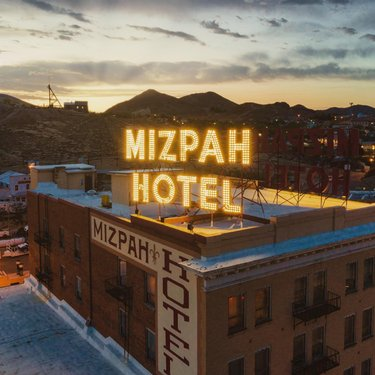 𝗧𝗵𝗲 𝗠𝗶𝘇! 👻 😱🤙 • • • Since 1907, the Mizpah Hotel has been an oasis of comfort in the stark beauty of Nevada's high desert.  Built for $200,000, with solid granite walls, leaded glass windows and Victorian-era luxury appointments, the hotel featured solid oak furniture, hot and cold running water, steam heat, brass chandeliers, stained glass windows, and an electric elevator (one of the first in the state). At five stories, it was also the tallest building in Nevada at the time.   The Mizpah is known as the most haunted hotel in the USA. All sorts of crazy stuff happened out there back in the day.  The Lady in Red is the most popular ghost that haunts the hotel. The story goes that she was a high class prostitute who was strangled by a client. You can book the room she was strangled in if that is your thing. There is a nameless soldier that is said to haunt the 3rd and 4th floors of the hotel. A pair of children are also known to haunt the 3rd floor and play pranks on guest. There have been reports of guest hearing giggling in the hallways when no one is around and doors opening and closing without explanation. • • • #themizpah #mizpah #mizpahhotel #hauntedplaces #hauntedhotel #tonopah #tonopahnevada #travelnevada #nevada #nv #onlyinnevada #paranormalactivity #retrosigns #retrosign #hauntedplaces #historichotel #hauntedhistory #hauntedlocations #explorenevada #nevadahistory #djimavicair2 #mavicair2 #wildwest #ghoststories #paranormal #ghostadventures #visitnevada #jrodphoto