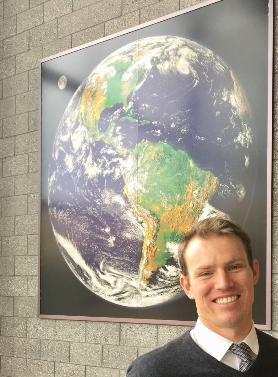 Photo of AJ in front of a map of the globe