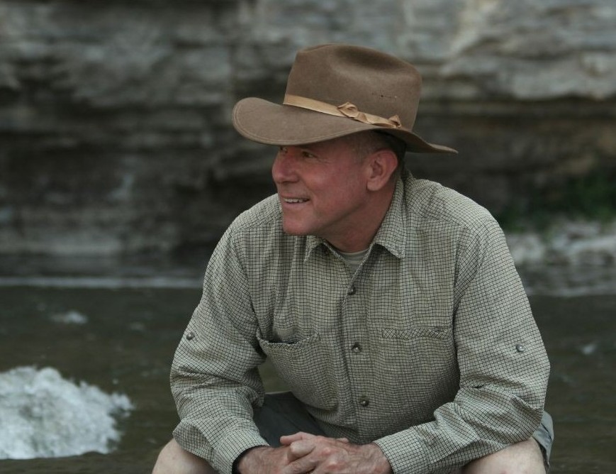 Dr. John Olson pictured sitting by a river