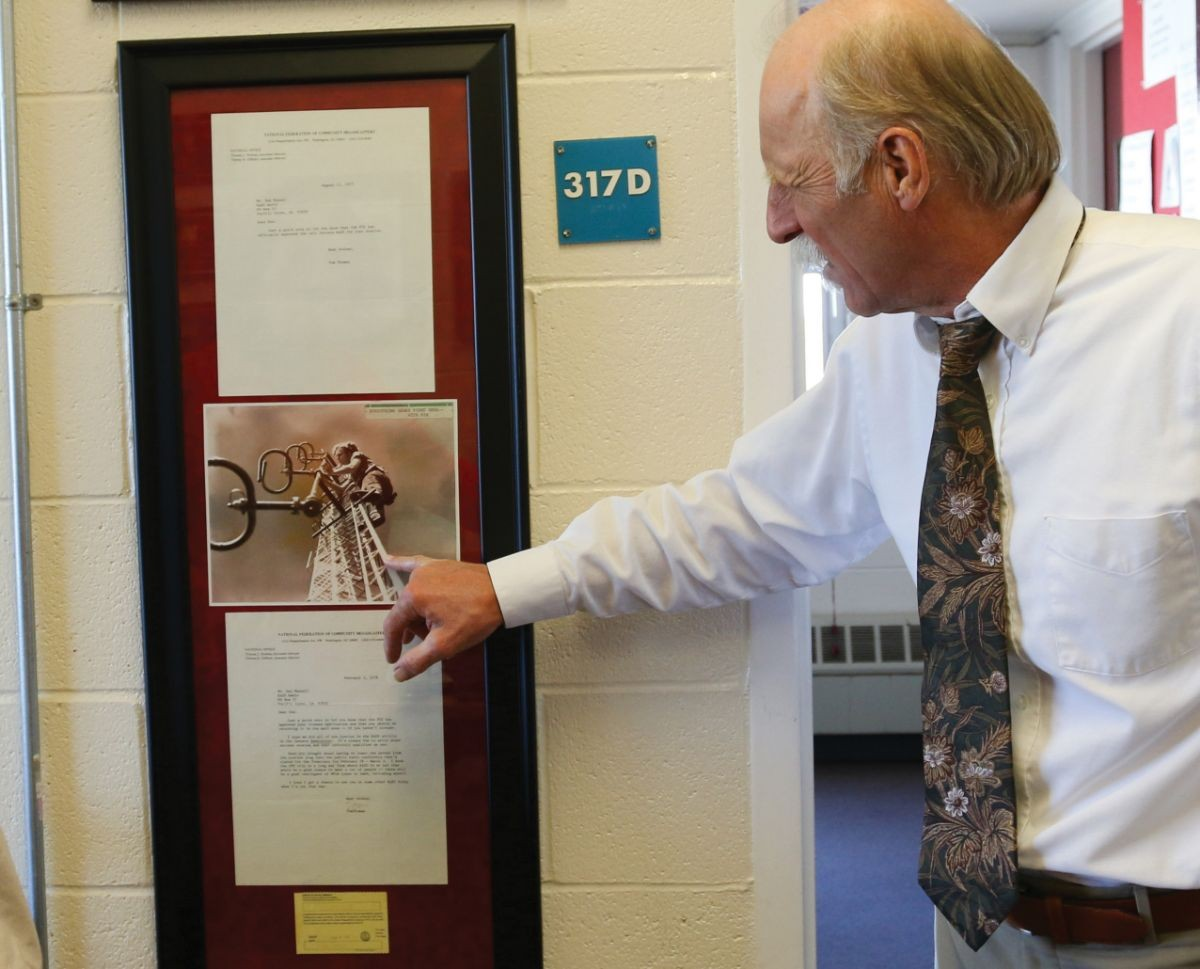 General manager Mik Benedek looks at a photo of station founder Don Mussell.