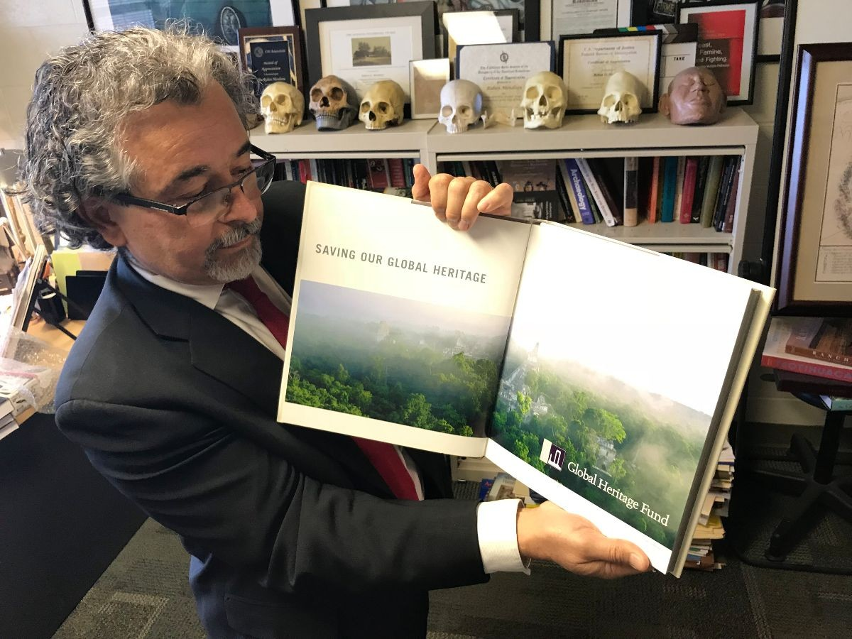 Mendoza holds a book showing Tikal