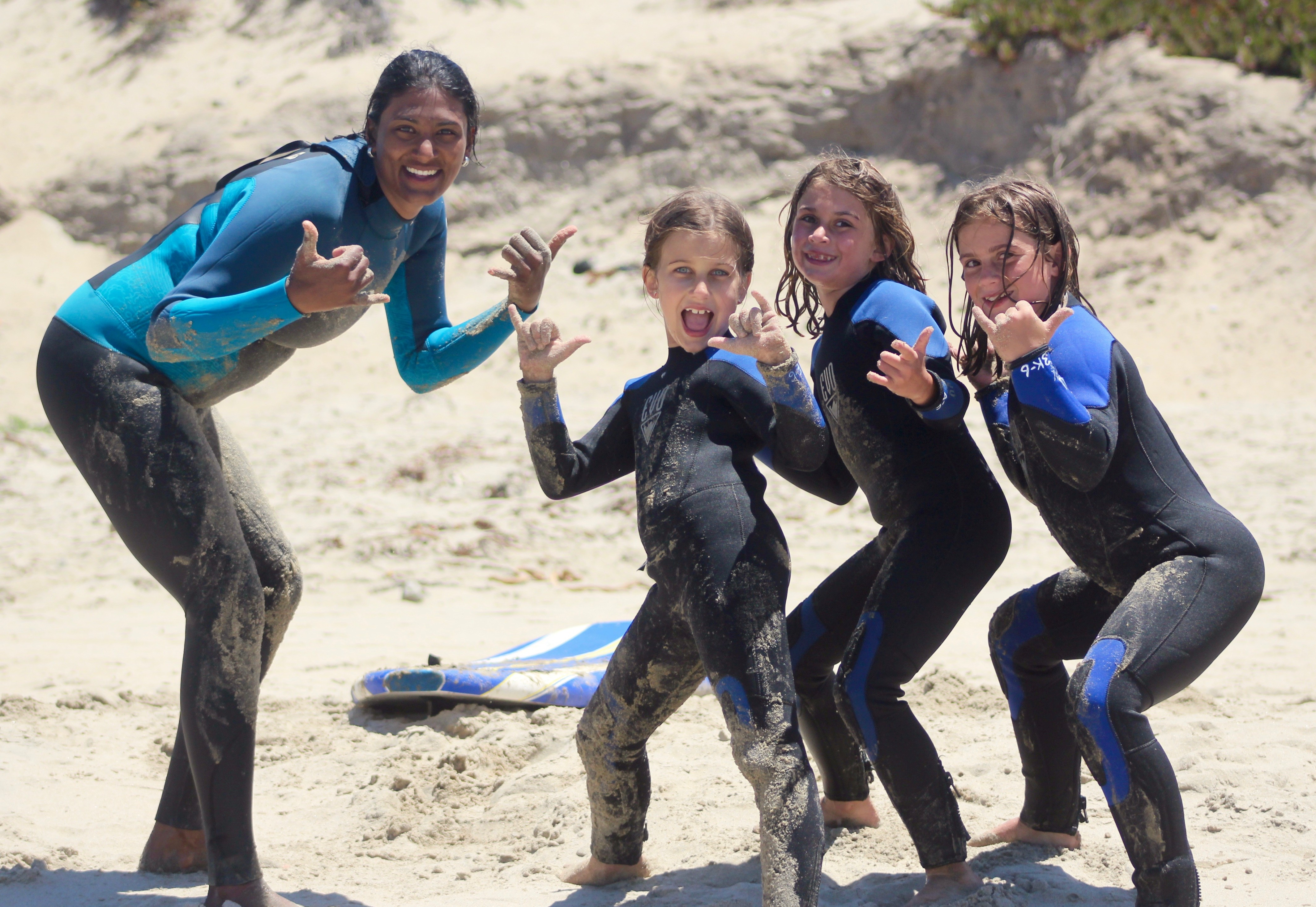 Campers in wetsuits posing with counselor