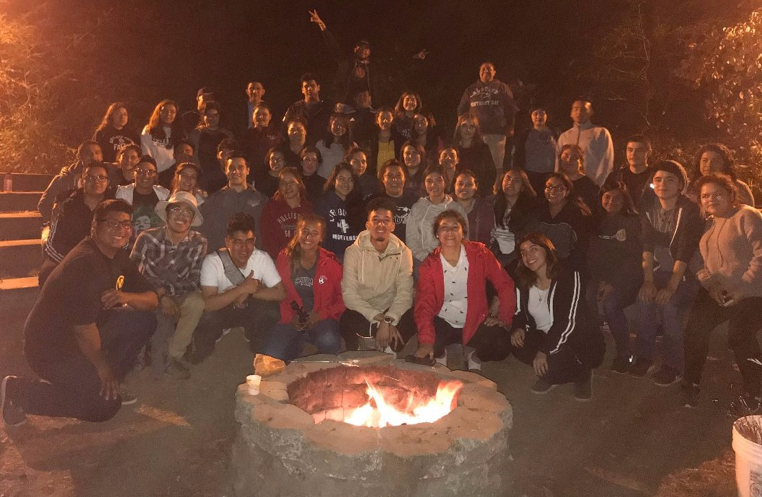 The 2017-2018 CAMP Cohort and staff posing for a group picture by the bonfire