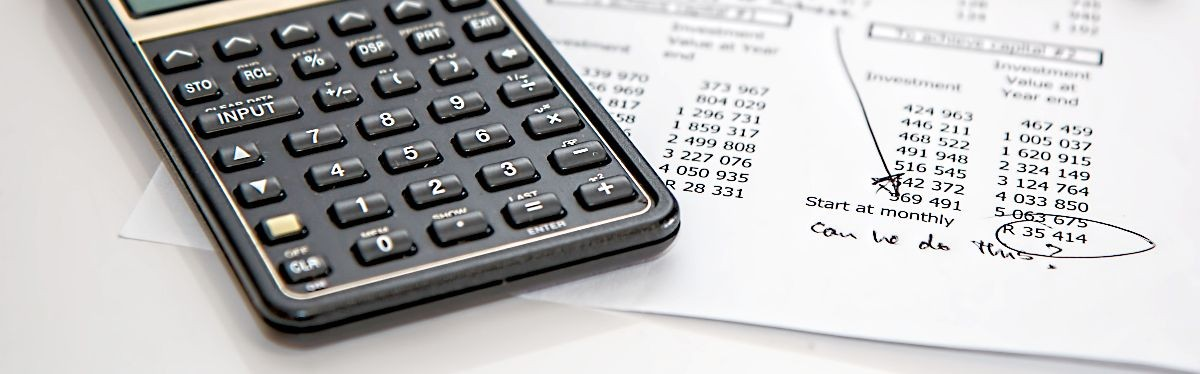 Photo of calculator next to a paper with a list of expenses.
