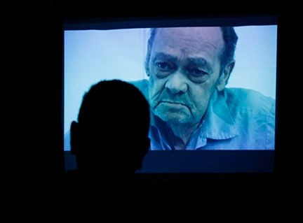 A viewer watches the story of Jack Hall (on screen) at the event.