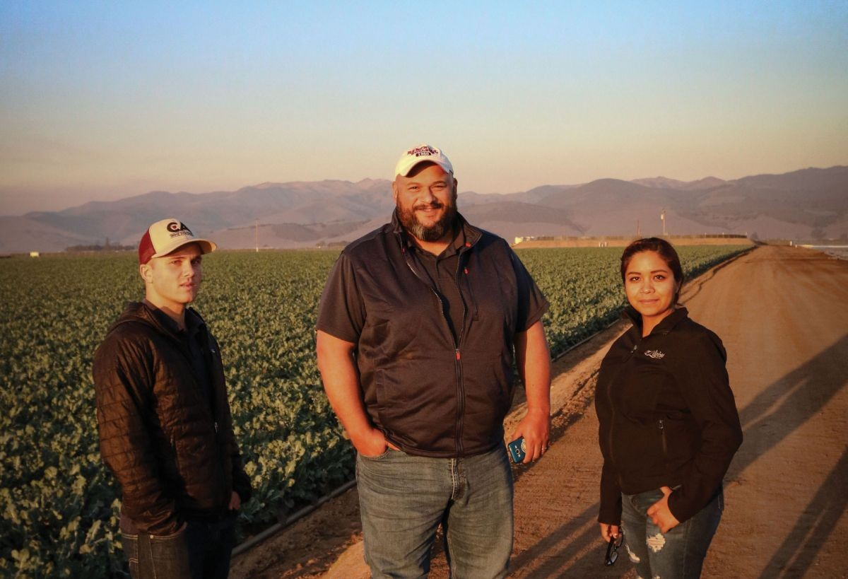 Three HeavyConnect employees standing next to a lush green field of broccoli.