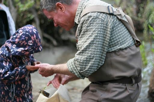 John Olson studying a critter with a child in a creek.
