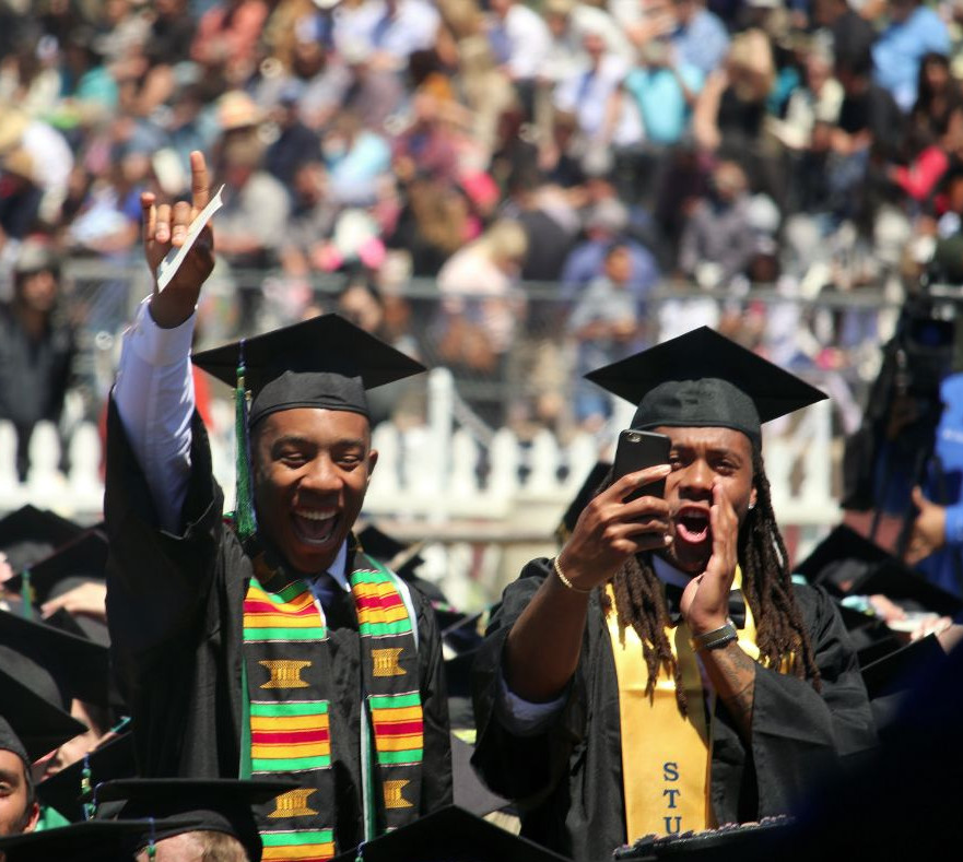 Two students cheering during 2017 commencement ceremony.