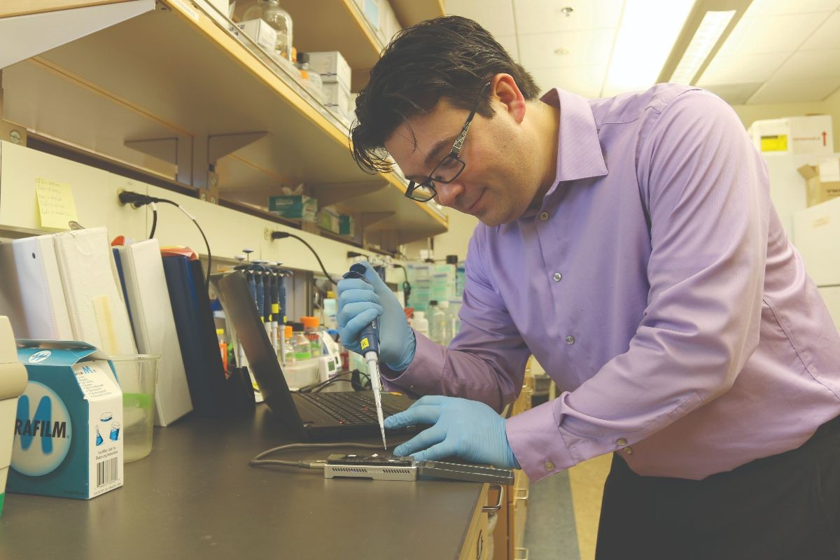Nate Jue in his lab working with hardware