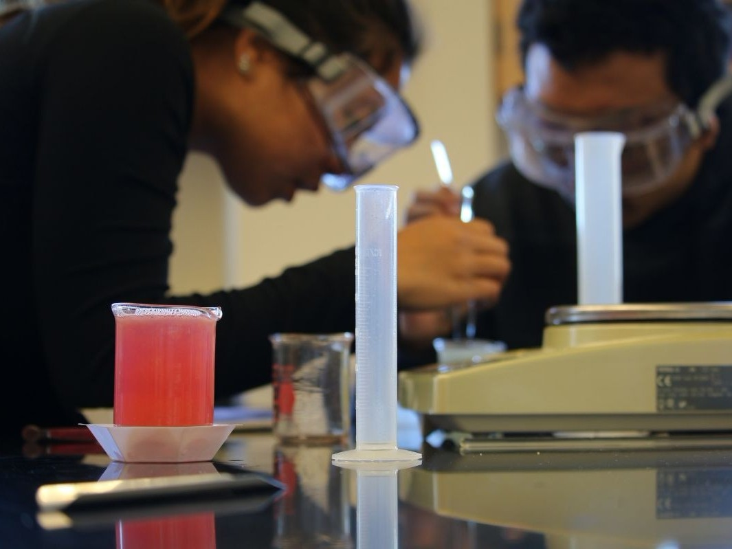 student performing experiment with focus on reagent in beaker