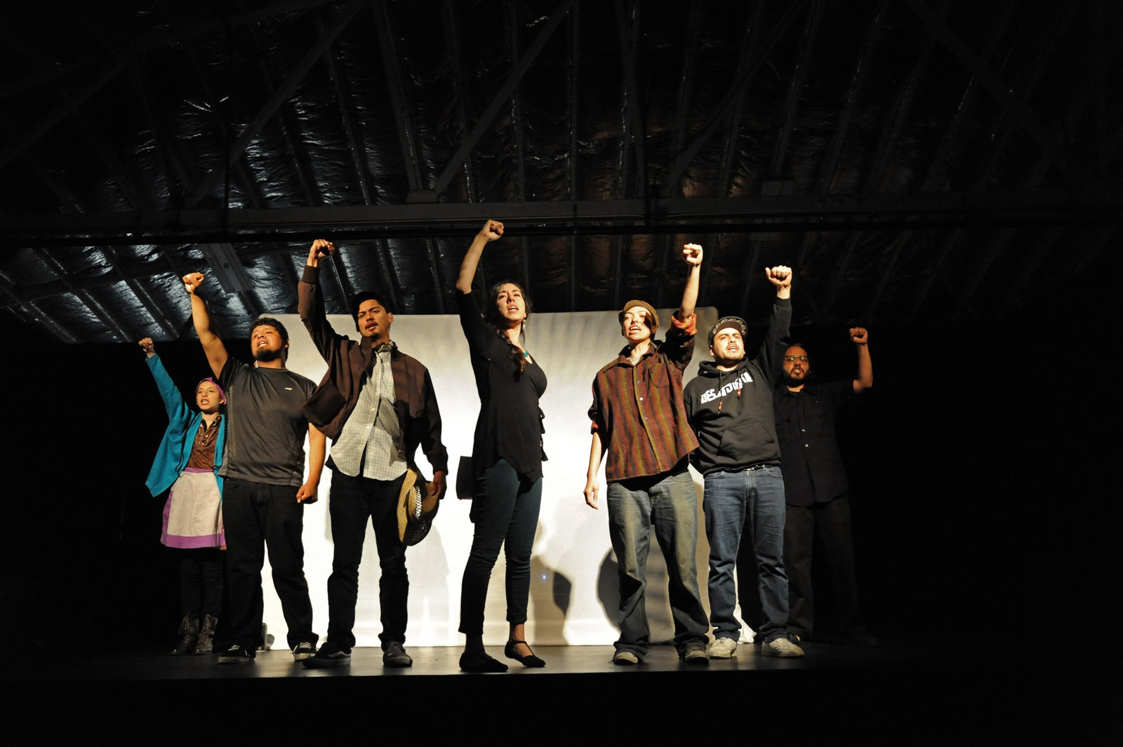 A group of students/actors from Artist ink on a stage performing.
