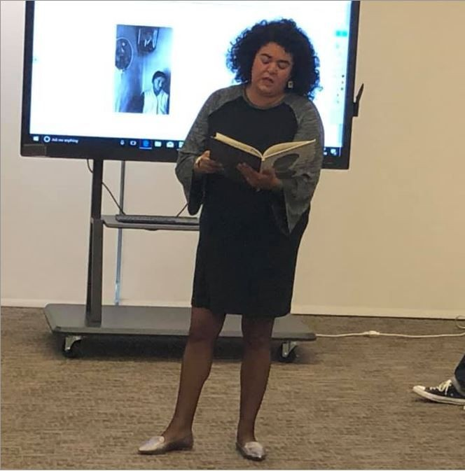 Woman is standing in front of audience reading a poem