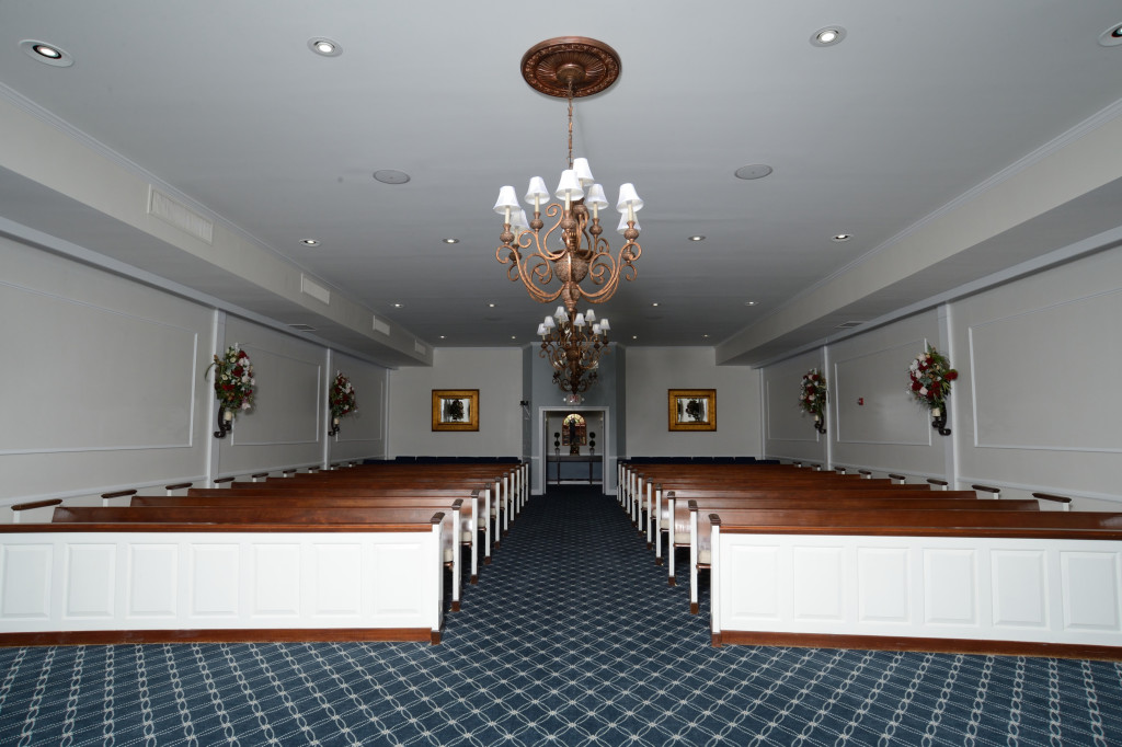 Josiah S. Everly Memorial Chapel looking towards rear entrance proudly boasts a newly drywalled ceiling, copperized chandelier medallions, architectural trim details, refinished pews newly set at an engaging angle, and color coordinated wall-mounted floral arrangements with electric candles.  All this, plus the bright new paint really make this an inviting space for persons of any faith.